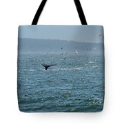 A Whale's Tail Above Water With Sail Boat In The Background Tote Bag