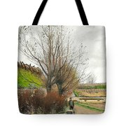Autumn Weather. A Man With A Wheelbarrow On A Path Tote Bag