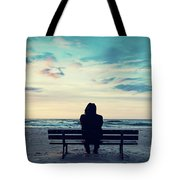 Man In Hood Sitting On A Lonely Bench On The Beach Tote Bag