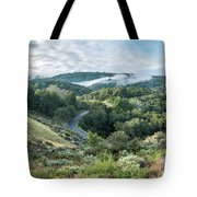 View Of Curved Road Through Dense Forest Area With Low Clouds Ov Tote Bag