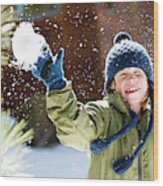 A Boy Throws A Snowball While Playing Wood Print