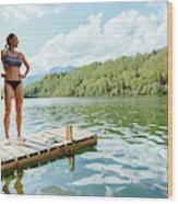 A Woman Is Standing On A Jetty Wood Print