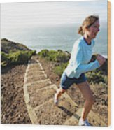 A Woman Running Stairs Near The Ocean Wood Print