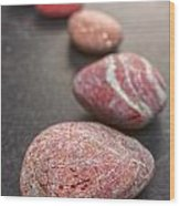 Curving Line Of Red And Grey Pebbles On Dark Background Wood Print by Colin and Linda McKie