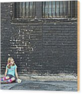 Girl Sitting On Ground Next To Brick Wall Wood Print