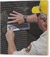 Man Getting A Rubbing Of Fallen Soldier's Name At The Vietnam War Memorial Wood Print