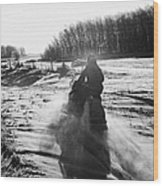 man on snowmobile crossing frozen fields in rural Forget Saskatchewan Canada Wood Print by Joe Fox