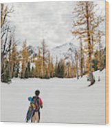 A Backpacker Hikes Through Snow Wood Print