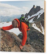 A Climber Scrambles Up A Rocky Mountain Wood Print