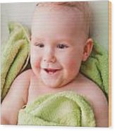 A Happy Baby Lying On Bed In Green Towel Wood Print