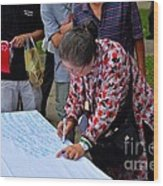 A Lady Signs Petition At May Day Rally Singapore Wood Print