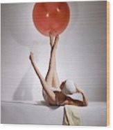 A Model Balancing A Red Ball On Her Feet Wood Print