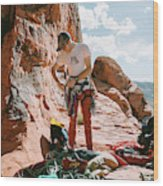 A Rock Climber Setting Up To Climb Wood Print