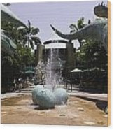 A Water Fountain With Dinosaur Eggs And Dinsosaurs In Universal Studios Wood Print