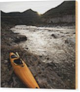 A Whitewater Kayak Rests On The Shore Wood Print