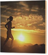 A Woman Jogs Under Sunset Wood Print