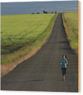 A Woman Running On A Dirt Road Wood Print