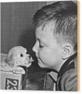 A Young Boy Is Face To Face With A Puppy Tongue. Wood Print
