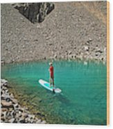 A Young Male Paddleboarding On A Small Wood Print