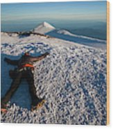 An Exhausted Climber Lies On The Summit Wood Print