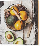 Basket With Avocado, Oranges And Dates Wood Print