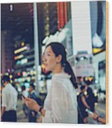 Beautiful Asian woman using mobile phone while crossing road in busy downtown city street at night Wood Print
