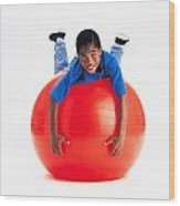 Boy Balancing On Exercise Ball Wood Print by Ron Nickel