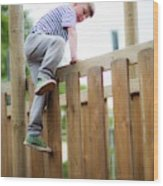Boy Climbing Over Wooden Fence Wood Print