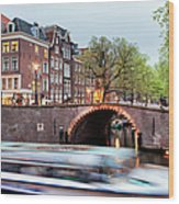 Canal Bridge And Boat Tour In Amsterdam At Evening Wood Print