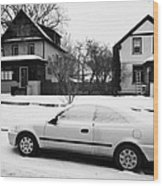 car covered in snow parked by the side of the street in front of residential homes caswell hill Sask Wood Print
