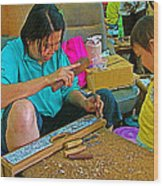 Child Watches As Mom Works In Teak Wood Carving Shop In Kanchanaburi-thailand Wood Print