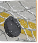 Close-up of an Ice Hockey puck hitting the back of the net as snow flies, front view Wood Print