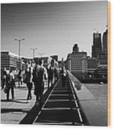 commuters and city workers cross london bridge over the river thames in the morning central London England UK Wood Print