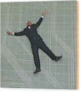 Conceptual Shot Of An African American Business Man As He Lays Flat On The Ground Holding His Phone Wood Print