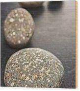 Curving Line Of Speckled Grey Pebbles On Dark Background Wood Print