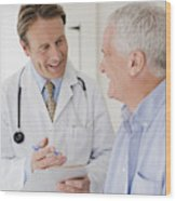Doctor talking with patient in doctors office Wood Print