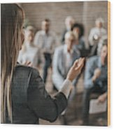 Female Manager Talking To Large Group Of Her Colleagues On A Business Seminar. Wood Print
