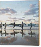 Five Surfers Walk Along Beach With Surf Wood Print