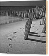 Footprints In The Sand Among The Pilings Wood Print