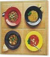 Four Dishes Of Different Food Wood Print