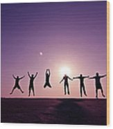 Friends Jumping Against Sunset Wood Print