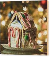Gingerbread House Against A Background Of Christmas Tree Lights Wood Print