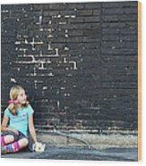 Girl Sitting On Ground Next To Brick Wall Wood Print
