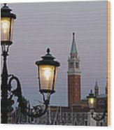 Lampposts Lit Up At Dusk With Building Wood Print