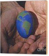 Man Holding Earth Egg Wood Print by Jim Corwin
