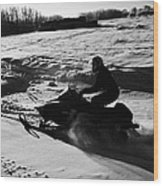 man on snowmobile crossing frozen fields in rural Forget Saskatchewan Wood Print by Joe Fox