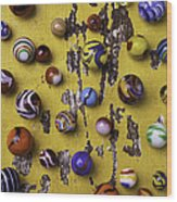 Marbles On Yellow Wooden Table Wood Print