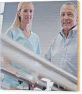 Nurse With Senior Man Using Parallel Walking Bars Wood Print