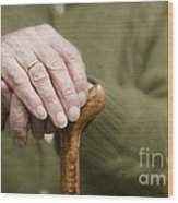 Old Hands Of A Senior On Walking Stick Wood Print