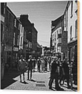 pedestrians walking down closed pedestrian area of quay street on sunny sunday afternoon Galway city Wood Print